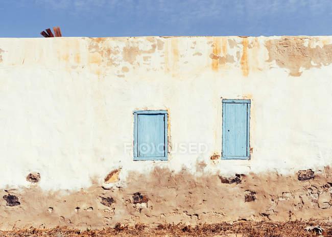 Finestre chiuse in muro rustico di vecchia casa — Foto stock