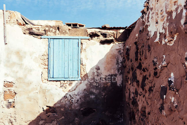 Window shuttered by blue wooden shutters in clay old wall of shabby ancient building in Fuerteventura, Las Palmas, Spain — Stock Photo