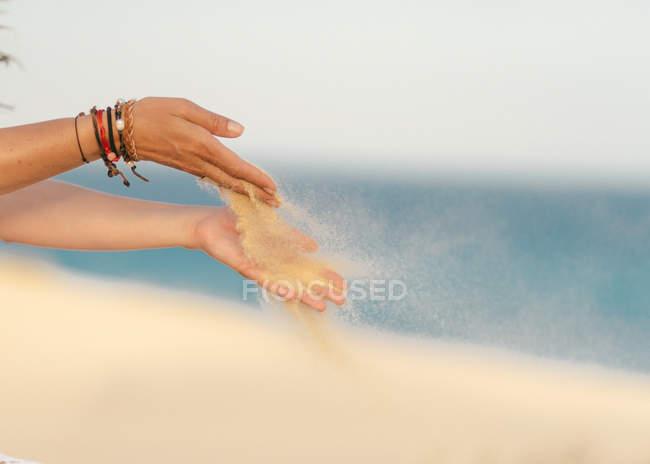 Gelber, sauberer Sand fliegt aus den Händen mit hellen Armbändern von Frauen am Strand von Fuerteventura, Las Palmas, Spanien — Stockfoto