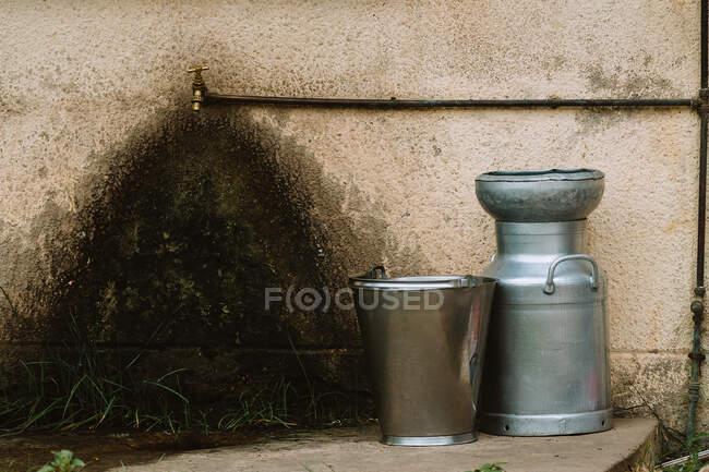 Vários recipientes metálicos colocados perto da parede do edifício pobre e torneira de água na rua da cidade na Gâmbia — Fotografia de Stock