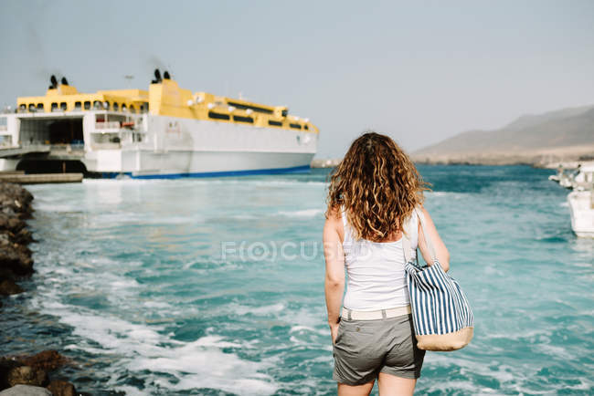 Curly woman looking at ship in water on seashore — Stock Photo