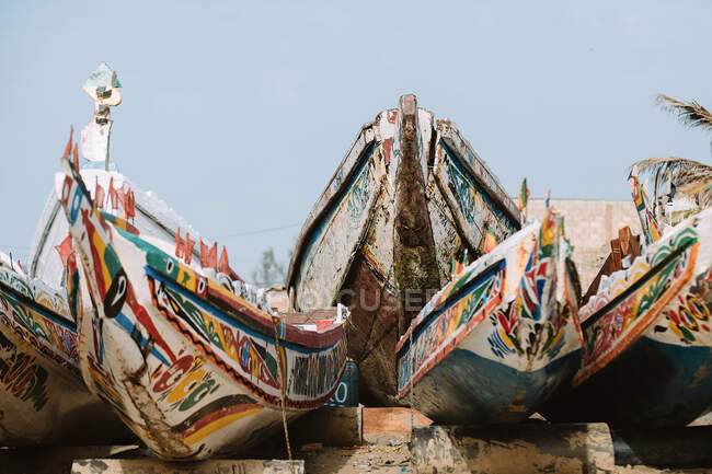 Navi intemperie con ornamenti colorati situati contro cielo blu senza nuvole nel porto della città in Gambia — Foto stock