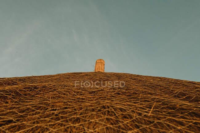 Desde abajo techo de paja amarilla de la casa de pueblo contra el cielo azul en Gambia - foto de stock