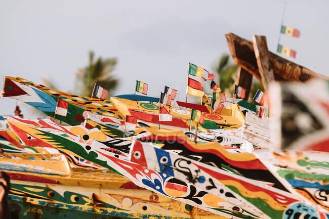 Barche da pesca in legno con frontali colorati e varie bandiere piccole situate nel porto della città in Gambia — Foto stock