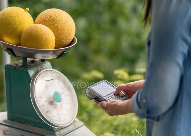 Imagem recortada da mulher pesando melões e faturamento ao usar terminal para contato com menos pagamento — Fotografia de Stock
