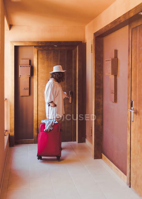 Woman in and casual white clothes with red suitcase closing wooden door in hotel corridor — Stock Photo