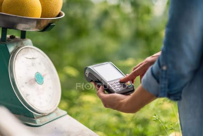 Обрезанное изображение женщины, взвешивающей дыни и выставляющей счета при использовании терминала для бесконтактной оплаты — стоковое фото