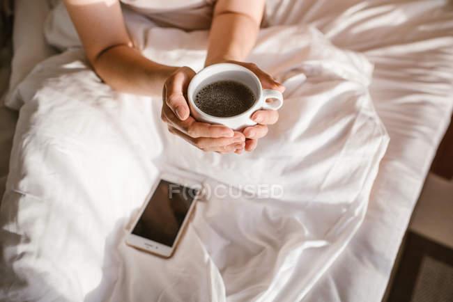 Сверху руки женщины, держащей чашку кофе во время использования смартфона в постели утром — стоковое фото