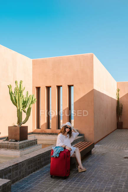 Woman in sunglasses touching hat while sitting alone and waiting on bench beside red suitcase near building — Stock Photo