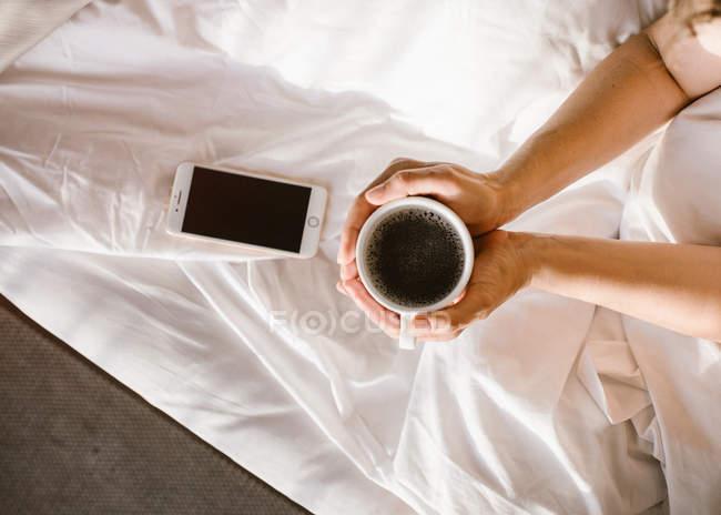 Da sopra le mani della donna che tiene la tazza di caffè durante l'utilizzo di smartphone a letto al mattino — Foto stock