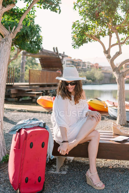 Tired woman in sunglasses and casual white clothes focusing and massaging feet while sitting alone on bench — Stock Photo