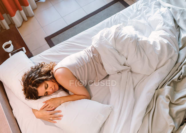 From above calm female sleeping in white bed near bedside table with round cup of coffee and smartphone in morning — Stock Photo