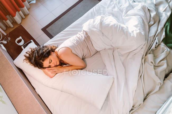 De cima calmo feminino dormindo na cama branca perto de mesa de cabeceira com xícara redonda de café e smartphone de manhã — Fotografia de Stock