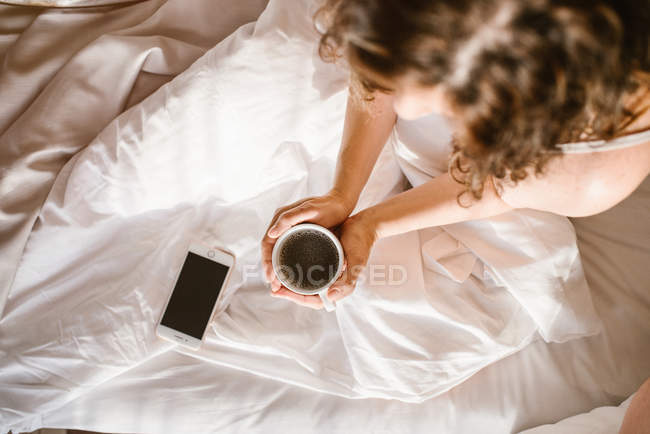 Dall'alto femmina adulta irriconoscibile che tiene la tazza rotonda di caffè a letto con smartphone al mattino — Foto stock