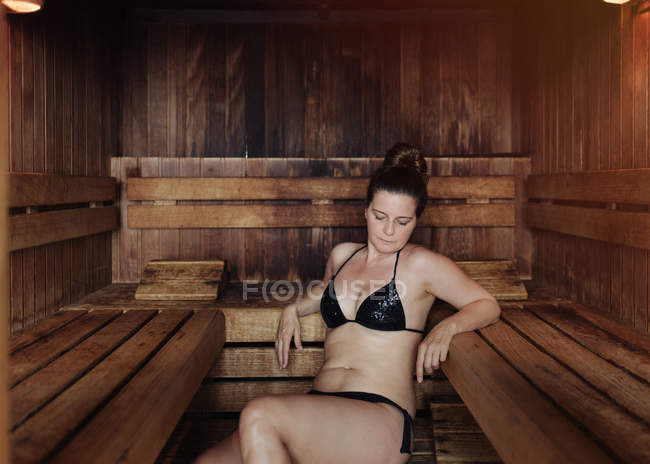 Donna in bikini nero seduta con gli occhi chiusi su un asciugamano in bagno turco appoggiata su una panchina di legno e godendo di calore — Foto stock