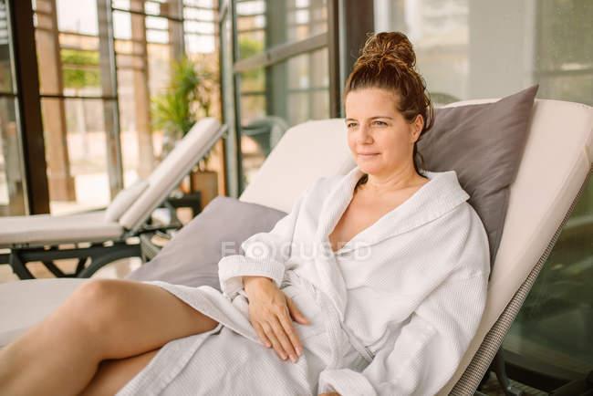 Взрослая женщина в белом халате лежит и смотрит на кровать после процедуры в современном салоне — стоковое фото