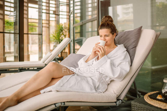 Positive woman in white bathrobe drinking water while lying on chaise lounge after spa procedure — Stock Photo