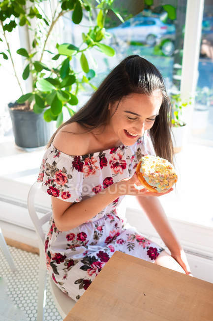 Content woman in sundress holding pastry with closed eyes while sitting at table by window — Stock Photo