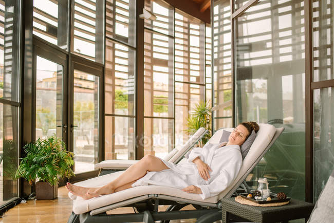 Бічний погляд дорослої жінки в білій халаті лежить з закритими очима на ліжко після спа - процедури в сучасному салоні. — стокове фото