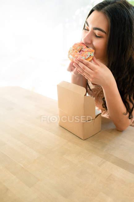Mujer feliz comiendo postre glaseado mientras está sentado en la mesa - foto de stock