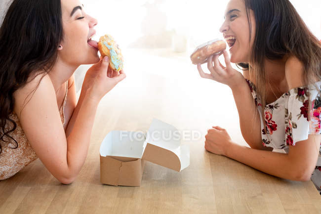 Happy women with box of glazed desserts sitting at table — Stock Photo