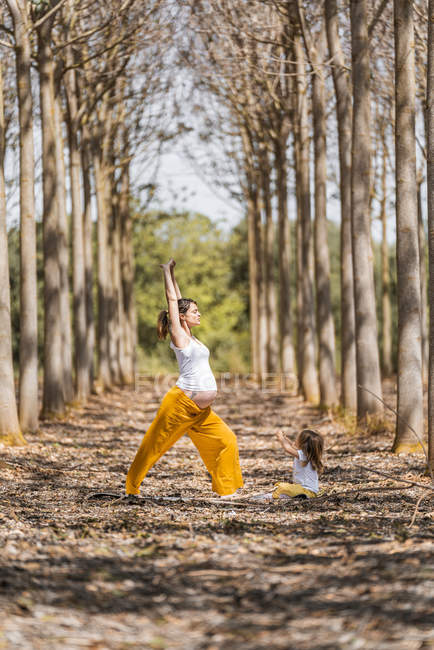 Cheerful pregnant mother and daughter practicing yoga in park during sunny daytime — Stock Photo