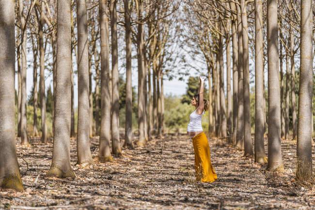 Взрослая будущая мать, практикующая йогу в парке в солнечную погоду — стоковое фото