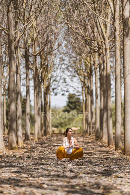 Femme enceinte adulte calme pratiquant le yoga tout en étant assis dans la pose lotus sur le sol dans le parc — Photo de stock