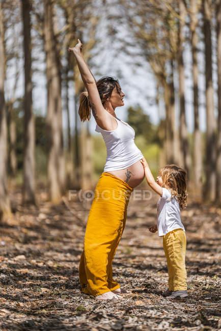 Embarazada madre e hija divirtiéndose en el parque - foto de stock