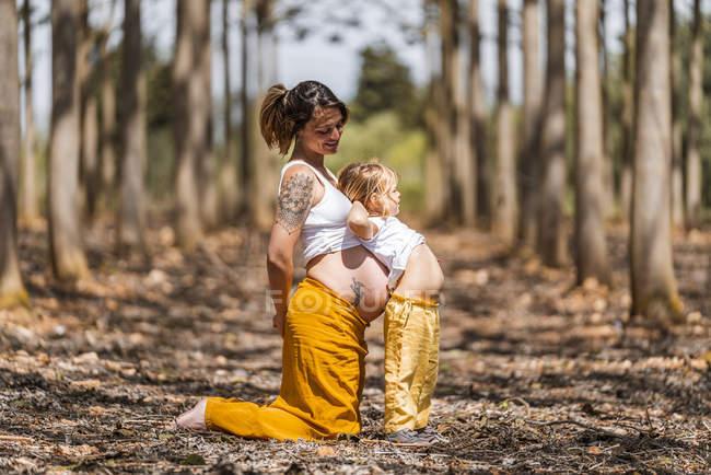 Беременная мать и маленькая дочь веселятся в парке — стоковое фото