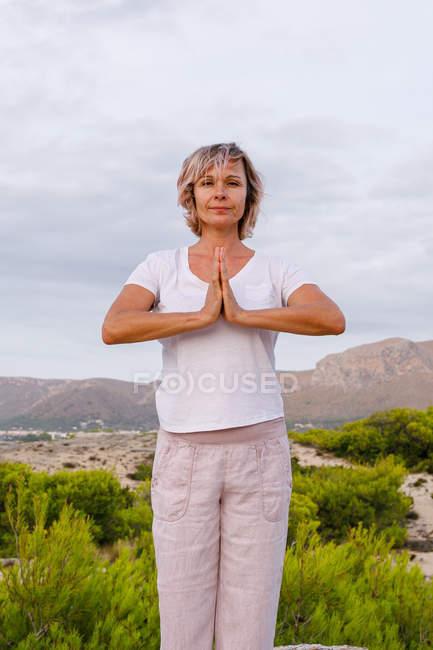Femme pieds nus méditant sur la pierre — Photo de stock