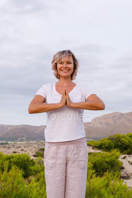 Босоногая женщина медитирует на камне — стоковое фото