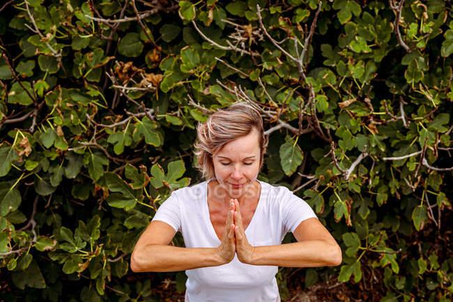 Взрослая женщина медитирует возле куста — стоковое фото