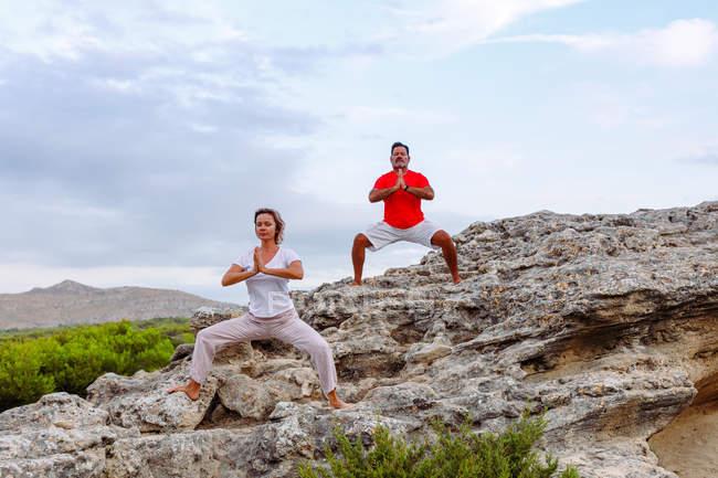 Paar meditiert auf Felsen — Stockfoto