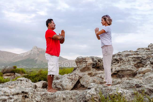 Couple meditating on rock — Stock Photo