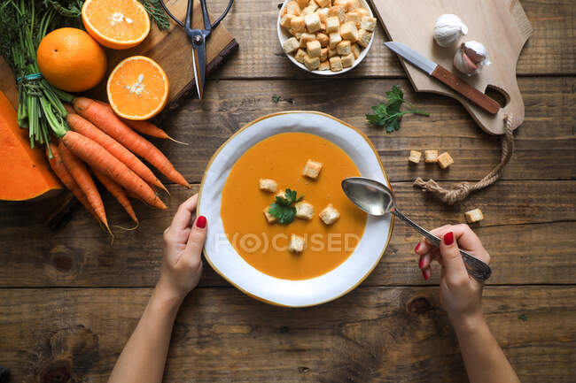 From above shot of unrecognizable person holding a bowl of orange carrot soup in a rustic wooden table with vegetables arrangements — Stock Photo