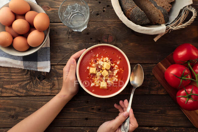 From above shot of unrecognizable person holding a bowl of red gazpacho in a rustic table with egg, bread, and fresh tomatoes arrangements — Stock Photo