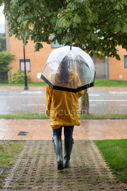 Back view of woman in yellow raincoat and dark rubber boots with transparent umbrella standing under rain in street — Stock Photo