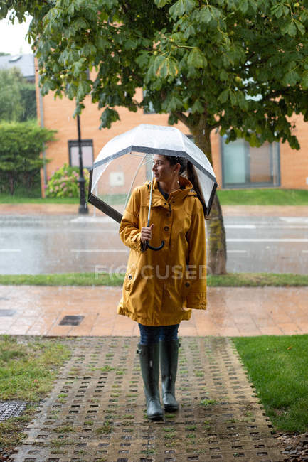 Young woman in yellow raincoat and dark rubber boots with transparent umbrella standing under rain in street and looking away — Stock Photo