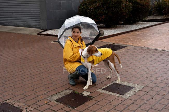 Mulher de casaco amarelo segurando guarda-chuva com ponteiro inglês em capa amarela na trela na chuva na rua — Fotografia de Stock