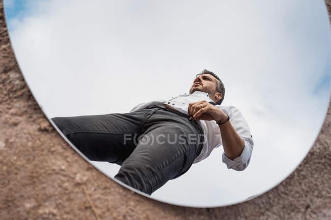 Vista de bajo ángulo del reflejo del hombre soñado en camisa y suspensores que se levantan sobre el cielo azul en espejo óvalo en suelo polvoriento. - foto de stock