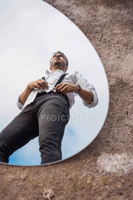 Low angle reflection of dreamy man in shirt and suspenders standing over blue sky in oval mirror on dusty ground — Foto stock