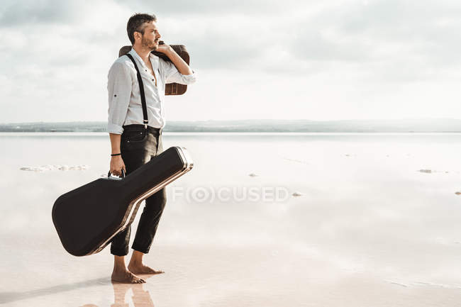 Side view of serious man in white shirt and suspenders carrying guitar and briefcase while standing barefoot in water by shore — Stock Photo