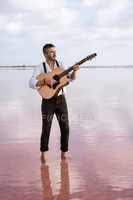 Leidenschaftlicher Mann in weißem Hemd und Hosenträgern, der am Ufer barfuß im Wasser steht und Gitarre spielt — Stockfoto