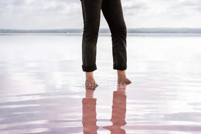 Partie basse de l'homme pieds nus en pantalon noir debout dans la mer calme par terre par temps nuageux — Photo de stock