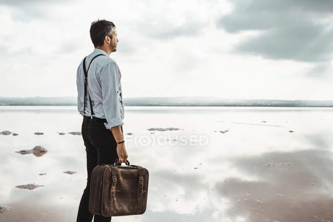 Боковой вид человека с потрепанным портфелем, стоящего босиком и смотрящего на мрачный пляж — стоковое фото