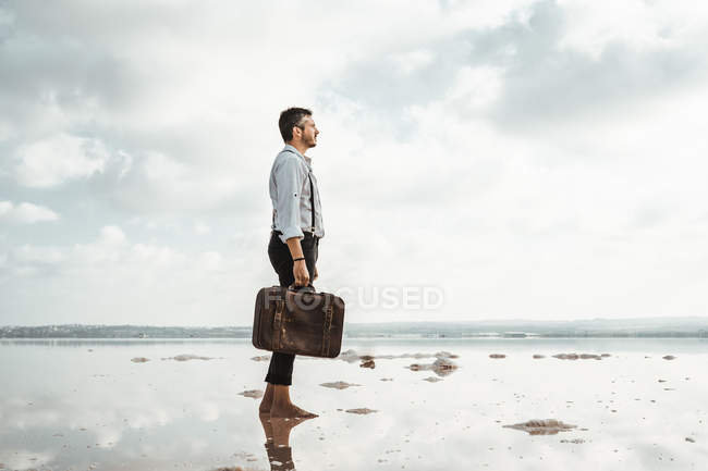 Side view of man carrying shabby briefcase while standing barefoot looking away on gloomy beach — Stock Photo