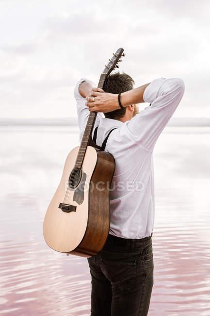 Von hinten Mann im weißen Hemd mit Akustikgitarre im Rücken, während er bei bewölktem Wetter an Land steht — Stockfoto