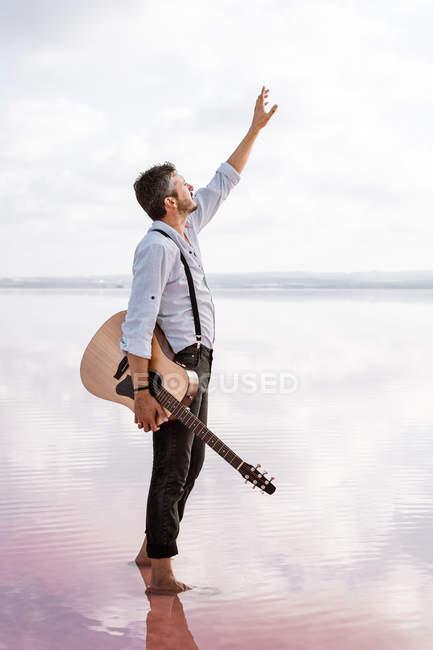 Melancholischer leidenschaftlicher Mann in weißem Hemd und Hosenträgern mit Gitarre, während er barfuß im Wasser steht und die Hand zum Himmel hebt — Stockfoto
