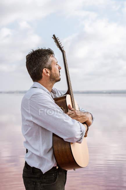 Melancholischer leidenschaftlicher Mann in weißem Hemd und Hosenträgern, der Gitarre umarmt, während er am Ufer im Wasser steht — Stockfoto